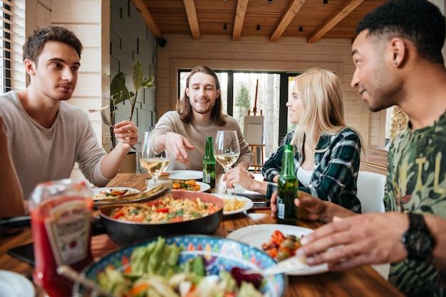 Grupa szczęśliwych uśmiechniętych wielorasowych przyjaciół jeść, pić i mówić