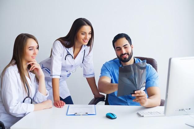 Grupa szczęśliwych wielorasowych lekarzy pracujących razem w klinice