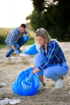 Grupa szczęśliwych wolontariuszy z obszarem czyszczenia worków na śmieci w parku