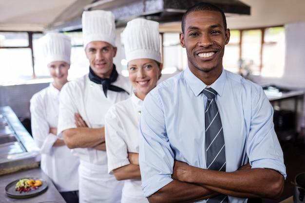 Grupa szefów kuchni i kierownik pozycja z rękami krzyżował w kuchni