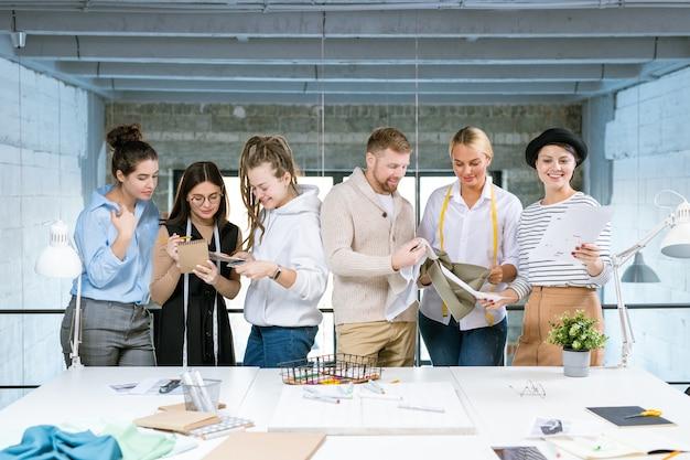 Grupa sześciu młodych kreatywnych projektantów stojących przy biurku podczas pracy nad nową kolekcją mody w studio