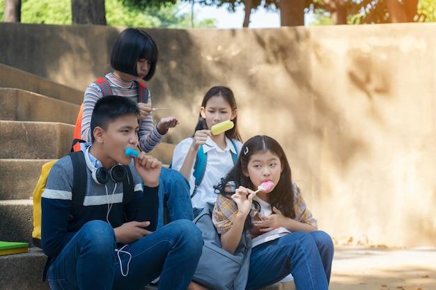 Grupa tajlandzcy ucznie je lody lody obsiadanie przy kampusem