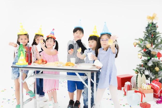 Grupa tajlandzko-azjatyckich dzieci je przekąski i dobrze się bawi na przyjęciu. z pudełkami i choinkami z boku i białym tłem