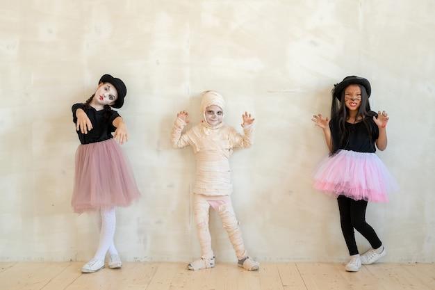 Grupa trzech artystycznych, wieloetnicznych dzieciaków w kostiumach na halloween, gestykulujących rękami na otynkowanej ścianie