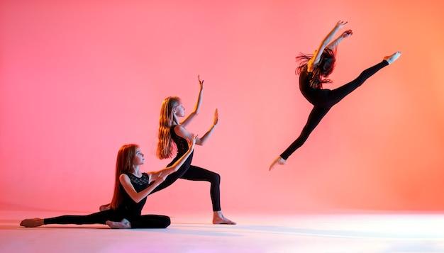 Grupa trzech baletnic o długich, rozwianych włosach w czarnych obcisłych garniturach tańczy na czerwonym tle