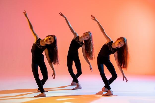 Grupa trzech baletnic w czarnych obcisłych garniturach tańczy na czerwonym tle