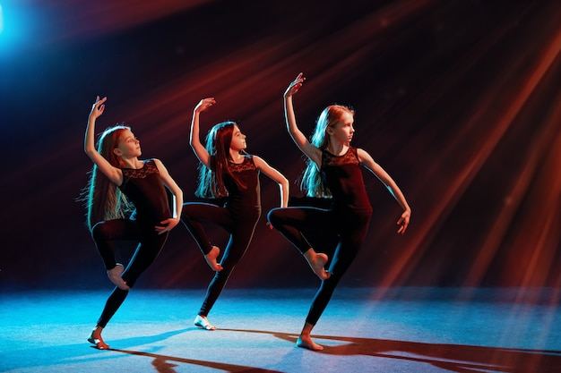 Grupa trzech baletnic w obcisłych kostiumach tańczy na czarnym tle