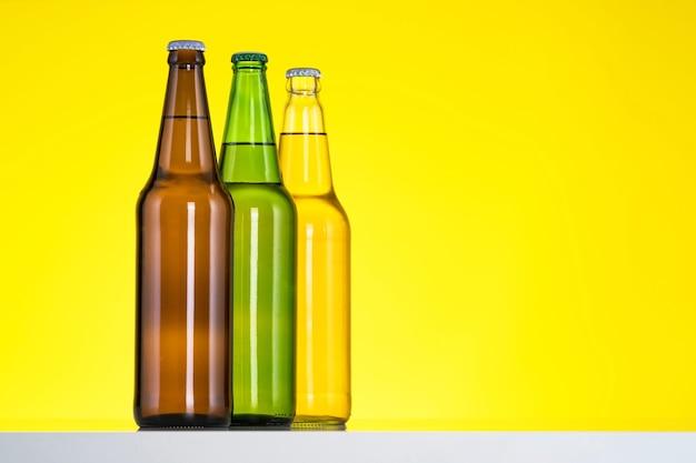 Grupa trzech butelek piwa na białym tle