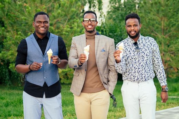 Grupa trzech czarnoskórych mężczyzn w stylowych garniturach na spotkanie w letnim parku. afroamerykanie przyjaciele hiszpanin biznesmen jedzenia waniliowych białych słodkich lodów w pikniku wafel róg na świeżym powietrzu.