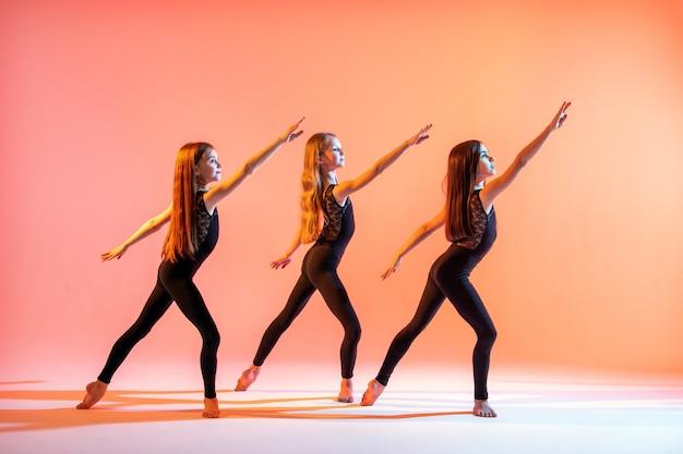 Grupa trzech dziewcząt w czarnych, obcisłych garniturach tańczy na czerwonym tle