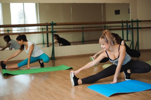 Grupa trzech dziewczyn robi ćwiczenia na siłowni.