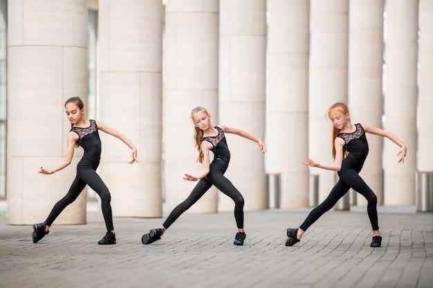 Grupa trzech małych baletnic w czarnych obcisłych kostiumach tańczy na tle pejzażu miasta.