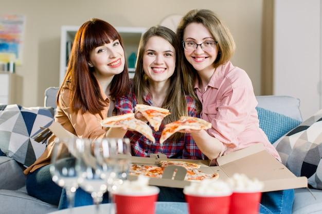 Grupa trzech młodych dziewczyn przyjaciół je pizzę podczas przyjęcia w domu. grupa młodych kobiet zabawy razem. szczęśliwe kobiety opowiada i śmia się podczas gdy jedzący włoskiego jedzenie i siedzący na leżance.