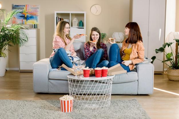 Grupa trzech młodych koleżanek z pizzy i popcorn świętuje w domowym wnętrzu