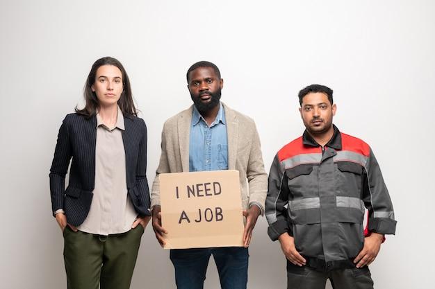 Grupa trzech młodych, międzykulturowych bezrobotnych ludzi stojących przy ścianie przed kamerą, podczas gdy jeden z nich trzyma notatkę o potrzebie pracy