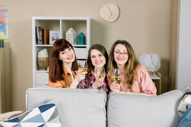 Grupa trzech młodych pięknych kobiet podnoszących kieliszki i wznoszących toast za wino. impreza dla dziewcząt w domu