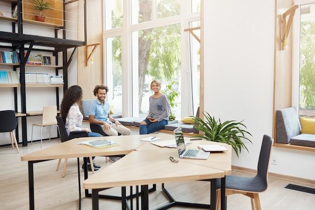 Grupa trzech młodych wieloetnicznych startupów pracujących razem w przestrzeni coworkingowej, mających przerwę od burzy mózgów. młodzi ludzie śmieją się, rozmawiają, dobrze się bawią