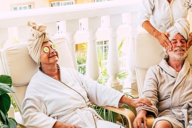 Grupa trzech osób i dwóch seniorów w ośrodku - dojrzała kobieta z cukinią na oczach - asysta wykonująca masaż twarzy emeryta
