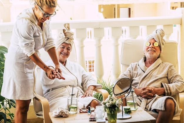 Grupa trzech osób i dwóch seniorów w resorcie - dojrzały mężczyzna z cukinią na oczach - asysta robi masaż dłonią emeryta