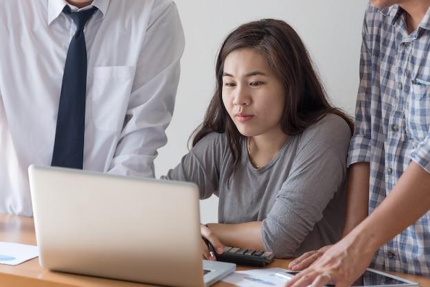 Grupa trzech partnerów biznesowych omawianie nowego projektu na posiedzeniu w sali biurowej, za pomocą laptopa. biznesmen koncentruje się na przeglądaniu prezentacji na ekranie laptopa. koncepcja wizji biznesowej