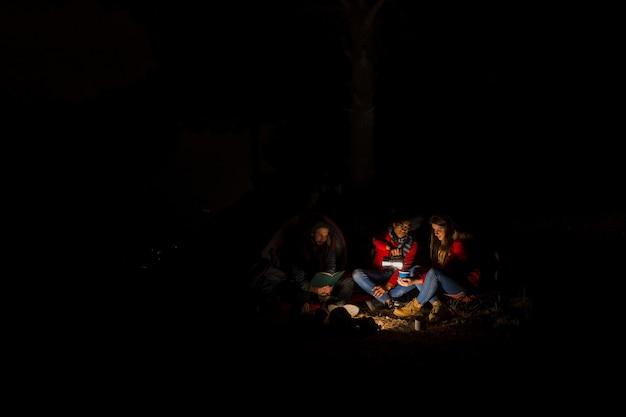 Grupa trzech przyjaciół camping w nocy