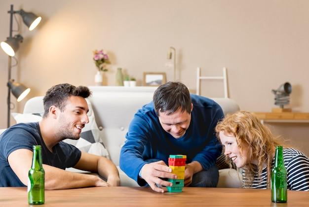 Grupa trzech przyjaciół grających w gry w domu