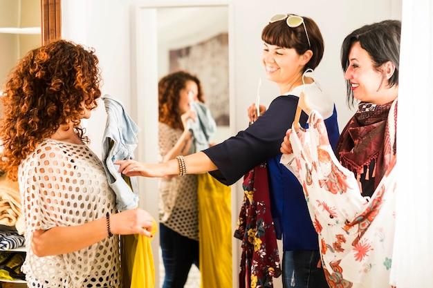 Grupa trzech przyjaciół rasy kaukaskiej, która wybiera odpowiednią sukienkę na imprezę lub zakupy na świeżym powietrzu. wnętrze domu z dużą ilością kolorowych sukienek i mnóstwem uśmiechów
