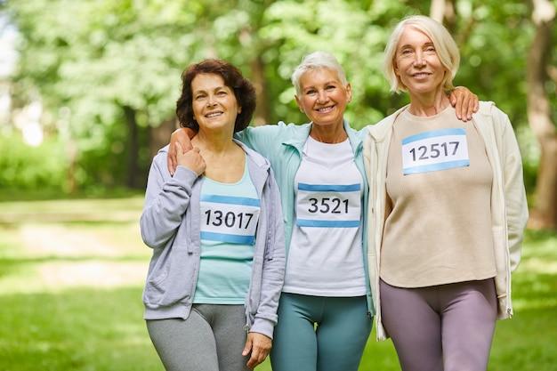 Grupa trzech radosnych koleżanek starszych biorących udział w wyścigu letniego maratonu stojących razem w parku uśmiechając się do kamery