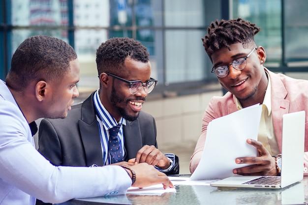 Grupa trzech stylowych afroamerykańskich biznesmenów partnerów przedsiębiorców w modnych garniturach biznesowych, siedzących przy stole, podpisujących papiery wartościowe z laptopem w letniej kawiarni na świeżym powietrzu