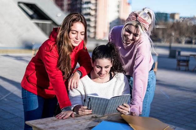 Grupa trzech szczęśliwych koleżanek wspominających swoje minione chwile podczas wspólnego czytania pamiętnika, zdziwiły się i śmiały