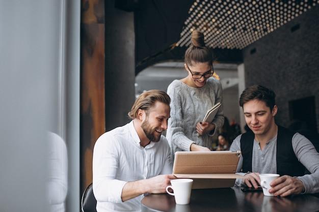Grupa trzy ludzie pracuje na projekcie na pastylce w kawiarni