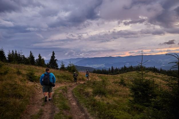 Grupa turystów chodzących na górskiej łące. widok na góry przed burzą. piesze wędrówki w karpatach