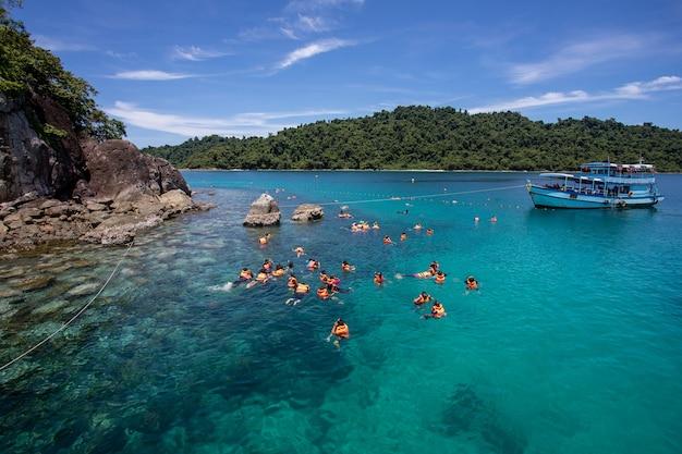 Grupa turystów nurkujących z rurką nad rafą koralową z czystą, błękitną wodą oceanu w tropikalnym czystym morzu