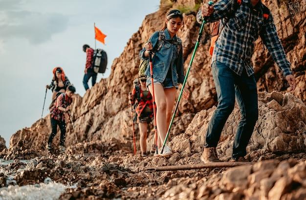 Grupa turystów schodzi ze szczytu góry przemierzając zbocze góry przez morze