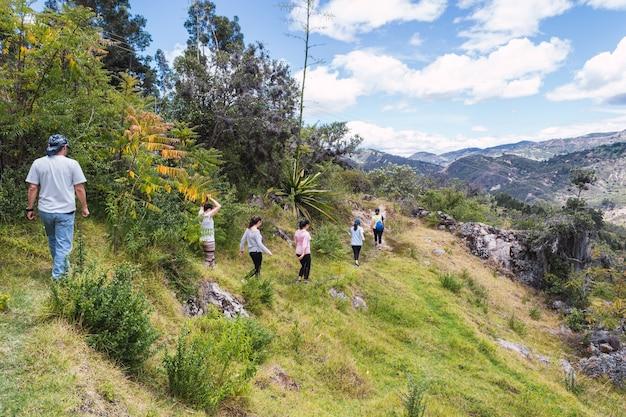 Grupa turystów spacerujących wąską ścieżką na górze