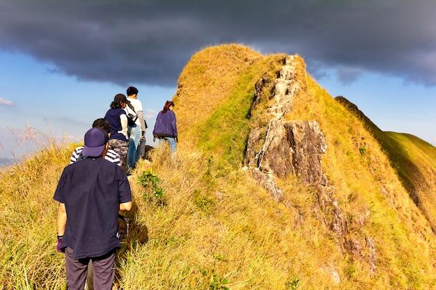 Grupa turystów stoi w kolejce, czekając na wspinanie się jeden po drugim.