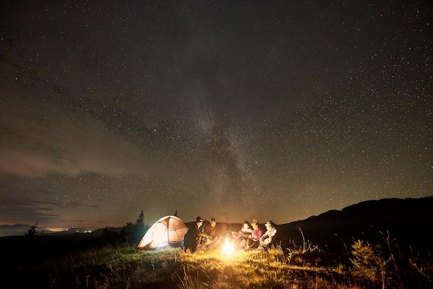 Grupa turystów z gitarą płonącą ogniskiem pod ciemnym rozgwieżdżonym niebem z konstelacją drogi mlecznej.