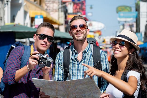 Grupa turystyczni backpacker przyjaciele podróżuje w bangkok tajlandia na wakacjach