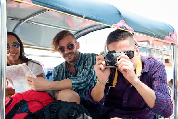 Grupa turystyczni przyjaciele bada bangkok miasto tajlandia na tuk tuk taxi