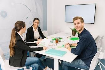 Grupa uśmiechnięci młodzi biznesmeni przy miejscem pracy