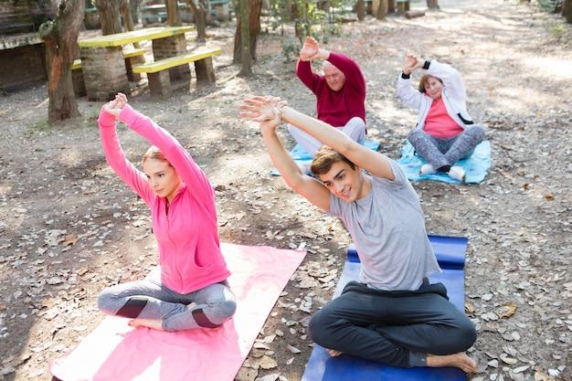 Grupa uczestniczy w zajęciach jogi w parku