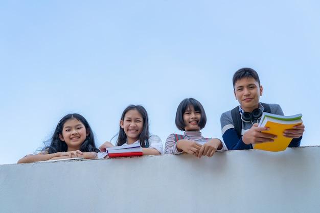Grupa uczni śmia się szczęśliwą pozycję wpólnie nad ściennym przejścia balckground buła niebem