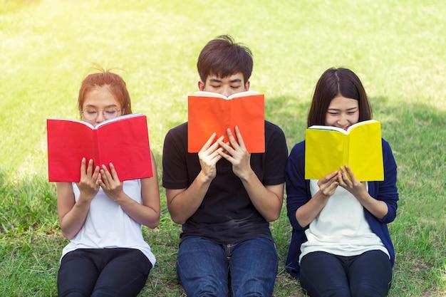 Grupa ucznie czyta na zielonej trawie w parku.