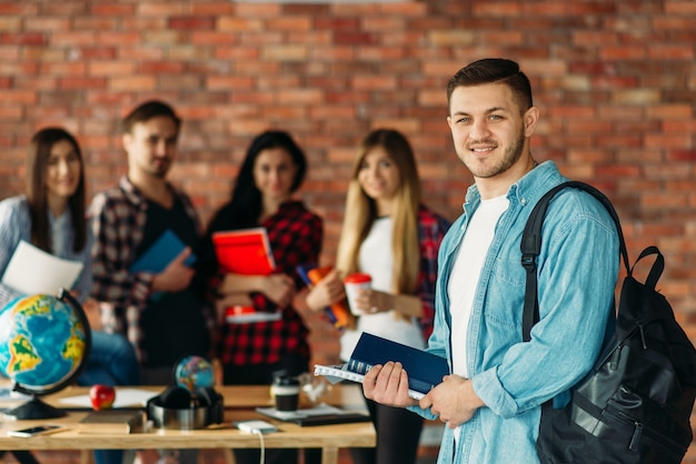 Grupa uczniów liceum z podręcznikami stojąca przy ścianie z cegły.