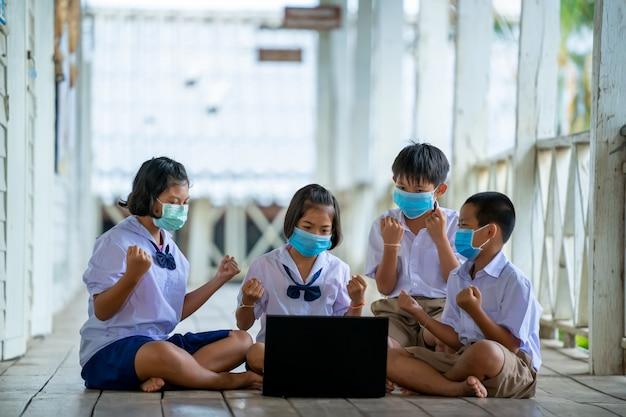 Grupa uczniów noszących maskę ochronną w celu ochrony przed covid-19 używa laptopa, aby szczęśliwie prowadzić lekcje online w tajlandzkiej klasie szkolnej.