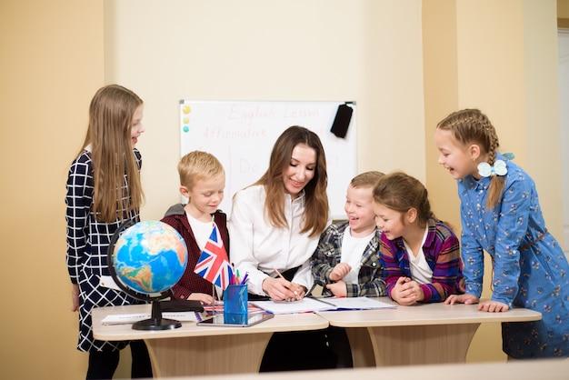 Grupa uczniów podstawowych i nauczyciela pracującego przy biurkach w klasie.