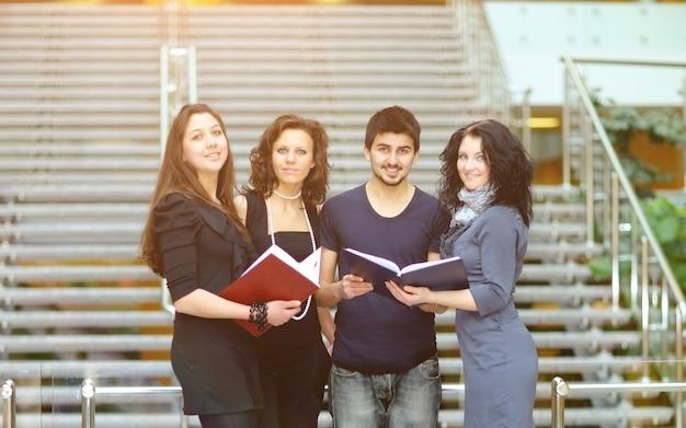Grupa uczniów rozmawiających i trzymających w rękach książki