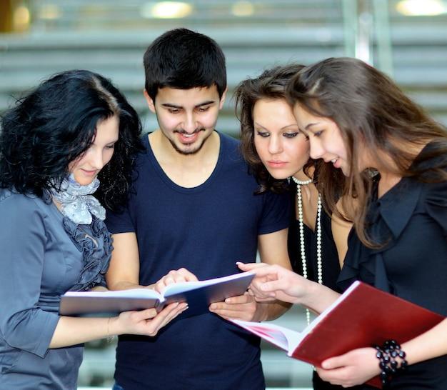 Grupa uczniów rozmawiających i trzymających zeszyty