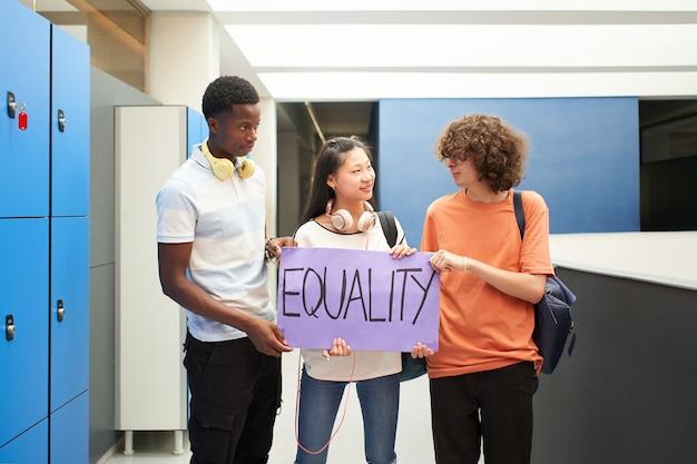 Grupa uczniów różnych narodowości niosących transparent w szkole protestujących o równość