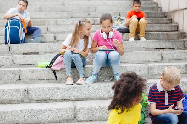 Grupa uczniów różnych narodowości w kolorowych ubraniach siedzi na kamiennych schodach. nastolatki rozmawiają, słuchają muzyki na słuchawkach, czytają książki.